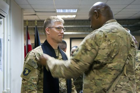 Master Sgt. Fredrick Murphy, right, master chaplain assistant, 101st Airborne Division (Air Assault) and Combined Joint Forces Land Component Command – Operation Inherent Resolve, adjusts the stole on Lt. Col. David Bowlus, outgoing 101st and CJFLCC-OIR chaplain, before a change of stole ceremony in Baghdad on May 30, 2016. (Sgt. Katie Eggers)