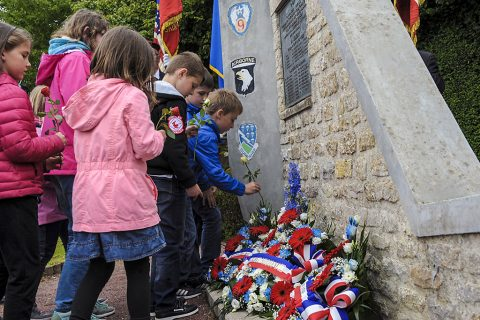 French children place flowers at the Currahee Memorial in Beuzeville au Plain, France, June 1, 2016. More than 380 service members from Europe and affiliated D-Day historical units are participating in the 72nd anniversary as part of Joint Task Force D-Day 72. (U.S. Air Force photo by Staff Sgt. Timothy Moore)