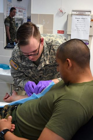 Specialist Bowman (center), a medic with the 230th Engineer Battalion, 194th Engineer Brigade, Tennessee Army National Guard, prepares to administer an IV during a medical training during Operation Resolute Castle on May 26, 2016 at Novo Selo Training Area, Bulgaria. As part of the exercise, Spc. Bowman was required to evaluate patients and administer IVs. (1st Lt. Matthew Gilbert, 194th Engineer Brigade)
