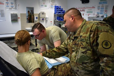 Specialist Bowman (center), a medic with the 230th Engineer Battalion, 194th Engineer Brigade, Tennessee Army National Guard, administers an IV while Captain Henry (right), a physician assistant with the Tennessee Army National Guard medical detachment supervises during Operation Resolute Castle on May 26, 2016 at Novo Selo Training Area. During the training exercise, Cpt. Henry created an environment where soldiers under his command were required to evaluate patients and administer IVs. (1st Lt. Matthew Gilbert, 194th Engineer Brigade)