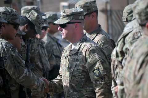Cpt. Justin Shaw, center, commander of Company D, 1st Battalion, 26th Infantry Regiment, Task Force Strike, shakes the hands of Soldiers of Company D after their patching ceremony June 3, 2016, in Taji, Iraq. Soldiers are allowed to wear the patch for the rest of their careers, signifying service in a theater of combat operations with the 101st Airborne Division (Air Assault). (1st Lt. Daniel Johnson)