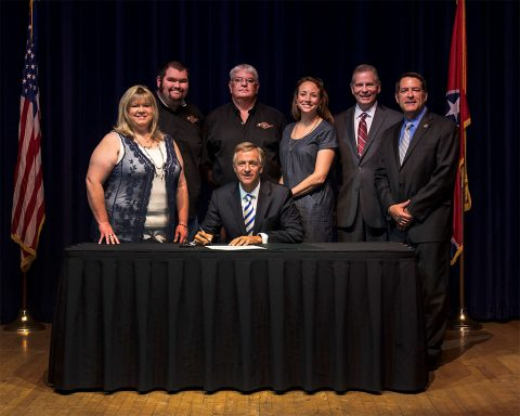 (L to R) Mother, Margaret Davis, son, (John) J.T. Davis, father, Brian Davis, Carrie Russell, State Representative Joe Pitts and Senator Mark Green. Pictured in front  Governor Bill Haslam.