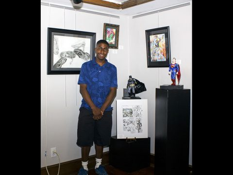 Pfc. Diandre L. Mosley, a unit supply specialist with 58th Signal Company, 101st Airborne Division Sustainment Brigade, 101st Airborne Division (Air Assault), stands in front of his artwork that is displayed at the Downtown Artists Co-op, Clarksville, TN. (Sgt. Neysa Canfield)