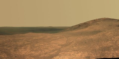 """Marathon Valley"" on Mars opens to a view across Endeavour Crater in this scene from the Pancam of NASA's Mars rover Opportunity. The scene merges many exposures taken during April and May 2016. The view spans from north (left) to west-southwest. Its foreground shows the valley's fractured texture. (NASA/JPL-Caltech/Cornell Univ./Arizona State Univ.)"