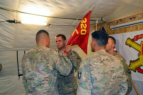 Lt. Col. Charles W. Kean, left, commander, of 1st Battalion, 320th Field Artillery Regiment, Task Force Strike, passes the Battery C guidon to Capt. Joseph Berlin, center, symbolizing his new authority as the commander of the battery at Kara Soar Base, Iraq, July 25, 2016. Battery C's mission in Iraq is to provide precision, surface-to-surface fires during Operation Inherent Resolve. (Maj. Ireka Sanders)