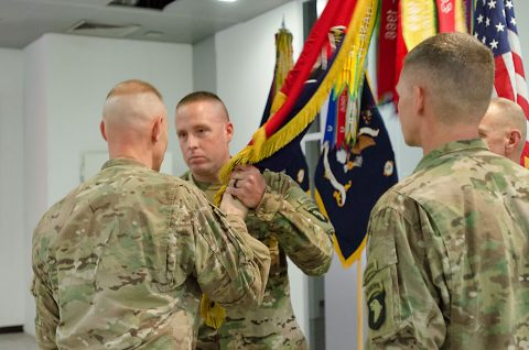 Col. Brett G. Sylvia, commander, 2nd Brigade Combat Team, 101st Airborne Division (Air Assault), passes the unit's colors to Command Sgt. Maj. John L. Wilson, incoming brigade command sergeant major, during a change of responsibility ceremony held July 23, in Erbil, Iraq. (Staff Sgt. Peter J. Berardi)