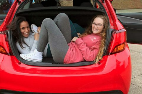 AP students at Northeast High School check out the trunk space of one of the cars to be given away on July 30th.