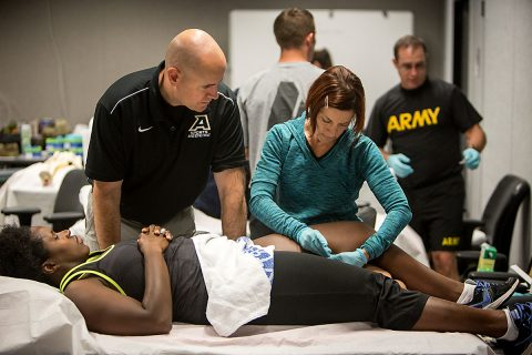 Under the instruction of Maj. Richard Westrick, U.S. Army Research Institute of Environmental Medicine's deputy chief of military performance, physical therapist Donna Gatto inserts a dry needle, one without medication or injection, through the skin and into areas of the muscle. As an American Red Cross volunteer, Gatto works at Byrd Clinic. (David E. Gillespie)