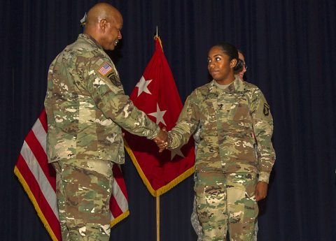 Lt. Gen. Larry D. Wyche, deputy commanding general for the United States Army Material Command, presents Spc. Iverem Wilson, a nodal network systems operator – maintainer with 58th Signal Company, 101st Special Troops Battalion, 101st Airborne Division Sustainment Brigade, 101st Abn. Div. (Air Assault), with a coin at Wilson Theater on Fort Campbell, Ky., Aug. 9, 2016, for her outstanding performance as Distinguished Honor Graduate from the Basic Leaders Course. (Sgt. Neysa Canfield, 101st Airborne Division Sustainment Brigade Public Affairs)