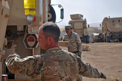 Staff Sgt. Vincent Boyd, left, a trainer with Headquarters and Headquarters Company, 2nd Battalion, 502nd Infantry Regiment, Task Force Strike, demonstrates to a Peshmerga soldier how to signal to properly hook a tow winch to another vehicle during vehicle recovery training, in Erbil, Iraq, June 22, 2016. U.S. and German personnel tested Peshmerga soldiers on proper vehicle recovery techniques during the training. (1st Lt. Daniel Johnson/Released)