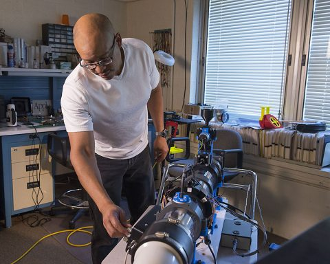 Electrical engineer Larry Greer sets up a homemade wind tunnel to test a saltation probe. (NASA)