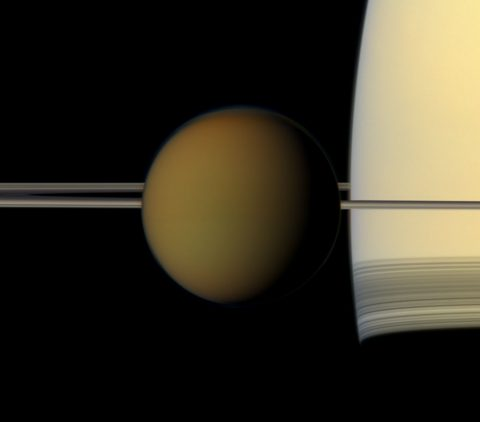 The hazy globe of Titan hangs in front of Saturn and its rings in this natural color view from NASA's Cassini spacecraft. (NASA/JPL-Caltech/Space Science Institute)