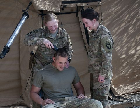 1st Lt. Amanda Veen, left, and 1st Lt. Katlin Forward, right, platoon leaders deployed with Company D, 39th Brigade Engineer Battalion, Task Force Strike, cut the hair of Spc. Mark Herron with Company C, 39th BEB, Sept,16, 2016 in Erbil Iraq. Forward, a cancer survivor, has joined with Veen to shave heads of Soldiers who want to show their support for cancer patients in the U.S. (1st Lt. Daniel Johnson)