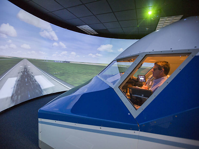 At NASA's Langley Research Center, retired airline pilots test procedures that will be used during upcoming flight tests of a new aircraft spacing tool. The simulator is set up like a 757 jet, similar to one of the aircraft in the ATD-1 flight tests. (NASA Langley / David C. Bowman)