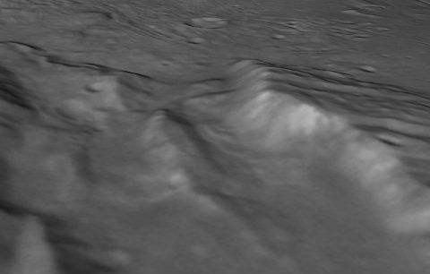 """Scientists from NASA's New Horizons mission have spotted signs of long run-out landslides on Pluto's largest moon, Charon. This perspective view of a chasm on Charon uses stereo reconstruction of images taken by two cameras on New Horizons, supplemented by a """"shape-from-shading"""" algorithm. (NASA/Johns Hopkins University Applied Physics Laboratory/Southwest Research Center)"""