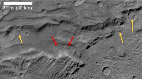 """Scientists from NASA's New Horizons mission have spotted signs of long run-out landslides on Pluto's largest moon, Charon. On this image of Charon's informally named """"Serenity Chasma,"""" from New Horizons' Long Range Reconnaissance Imager (LORRI), arrows mark indications of landslide activity. (NASA/Johns Hopkins University Applied Physics Laboratory/Southwest Research Center)"""