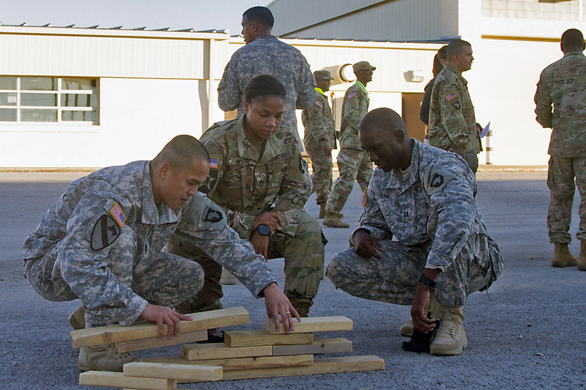 (L to R) Capt. Kenny K. Nguyen, Sgt. 1st Class Lashelle Webb, and Capt. Abdoul R. Kane, all with 101st Airborne Division (Air Assault) Sustainment Brigade, 101st Abn. Div., work together to properly place the blocks in the correct position, Nov. 9, 2016, with the help of their fourth team member, Maj. Jose G. Beltre (behind the group), who has an image of how the assembled pieces should look during the Command Team Physical Training Challenge at the 74th Composite Transportation Company motor pool on Fort Campbell, Ky. (Sgt. Neysa Canfield/101st Airborne Division Sustainment Brigade Public Affairs)