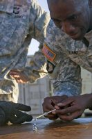 Capt. Abdoul R. Kane, commander for Headquarters and Headquarters Company, 101st Special Troops Battalion, 101st Airborne Division (Air Assault) Sustainment Brigade, 101st Abn. Div., attempts to place a third hex nut on a stack with a chopstick, Nov. 9, 2016, during the Command Team Physical Training Challenge at the 74th Composite Transportation Company motor pool on Fort Campbell, Ky. (Sgt. Neysa Canfield/101st Airborne Division Sustainment Brigade Public Affairs)