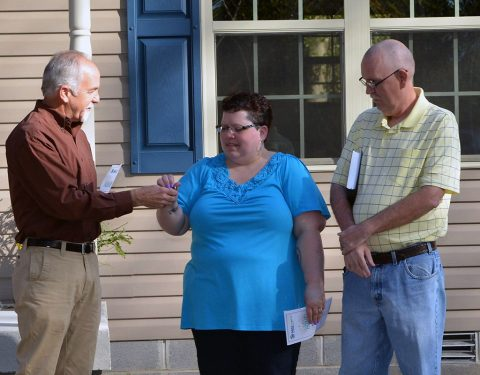 Rick Catignani, Board President, presents Susan Grasty with a new Bible and Herb Baggett, Founder and Board Member, presented the family with the keys to their new home.