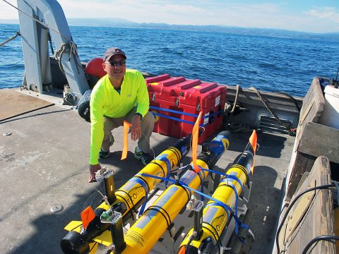 JPL's Steve Chien with several of the underwater drones used in a research project earlier this year. Chien, along with his research collaborators, are developing artificial intelligence for these drones. (NASA/JPL-Caltech)