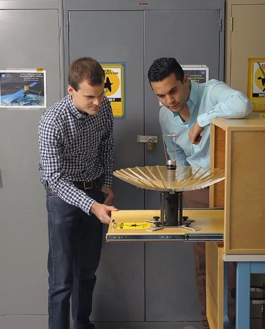 RainCube's radiofrequency lead Nacer Chahat (right) and mechanical engineer lead Jonathan Sauder (left) observe the CubeSat's deployed antenna. (NASA/JPL-Caltech)