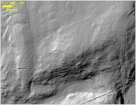 This bare-earth lidar image of a forest in Connecticut gives a view beneath the overgrown vegetation, where there are remnants of stone walls, building foundations, abandoned roads and what was once cleared farm land. Move the slider back and forth to see how lidar scans reveal distinctive features hidden beneath ground cover. (Katharine Johnson)