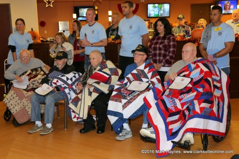 Veterans at Clarksville's Tennessee State Veteran's Home draped in their Quilts of Valor with members of the Sergeant Audie Murphy Association standing behind them.