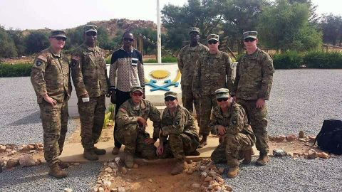 "The team from 2nd Battalion, 327th Infantry Regiment, of the 1st Brigade Combat Team ""Bastogne"", 101st Airborne Division (Air Assault), poses in front of the Nigerien Armed Forces basic training crest. Standing from left to right: Sgt. 1st Class Michael Mullins, Staff Sgt. Cameron Marsh, Interpreter Mr. Abdourahmane Ibrahim, Sgt. 1st Class Elocious Frazier, Sgt. 1st Class Sean Carey, 1st Lt. Dan Godlasky. Kneeling from left to right: Staff Sgt. Matthew England, Staff Sgt. Andrew Prince, First Sgt. Peter Russell. (Moussa Moumouni)"