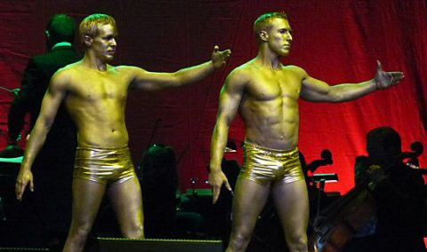 Golden men performing feats of flexibility and strength in smooth steady moves at the Cirque Musica Holiday Spectacular.