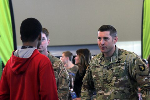 Chief Warrant Officer 1 Jason Emig, the network management technician for 101st Airborne Division (Air Assault) Sustainment Brigade, 101st Abn. Div., listens to a student asking questions about the communications career field of the military, Nov. 16, 2016, during the Eighth-Grade Career Exploration Day. (Sgt. Neysa Canfield/101st Airborne Division Sustainment Brigade Public Affairs)