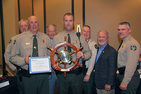 Brad Bagwell holds his award for being named the Boating Officer of the Year. Pictured (from left) are Lt. Jim Hooper, Col. Rider, Director Carter, Officer Bagwell, Lt. Col Moates, Chairman Cannon, and Cpt. Grandstaff.