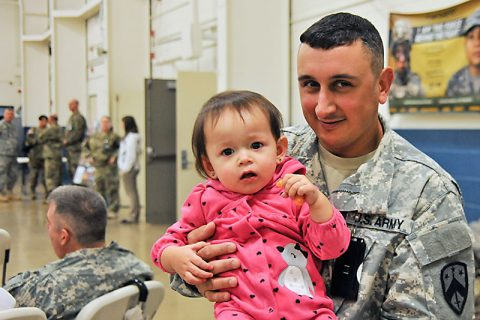 Staff Sgt. Aaron Canfield, of Nashville, says good-bye to his daughter during the farewell ceremony for the 230th Signal Company at Houston Barracks on December 4, prior to embarking on a one-year deployment to the Middle East. (Sgt. 1st Class Edgar Castro)