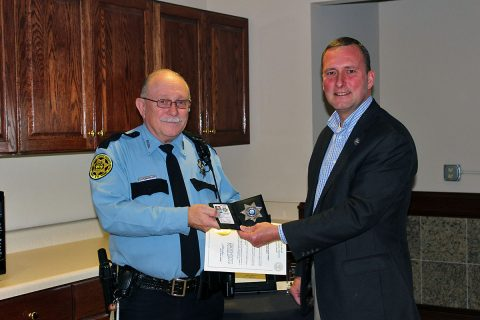 Montgomery County Sheriff John Fuson presents Deputy Frederick Ludwikowski with his badge and declaration.