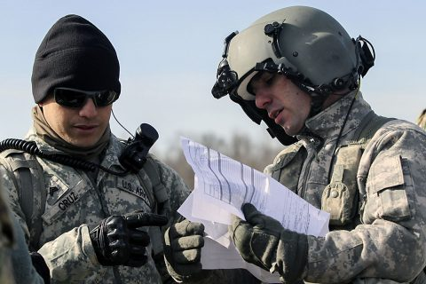 Sgt. Timothy Cruz, left, noncommissioned officer in charge of a sling load training operation for 58th Signal Company, 101st Special Troops Battalion, 101st Airborne Division (Air Assault) Sustainment Brigade, 101st Abn. Div., goes over paperwork with a CH-47 Chinook helicopter pilot from 101st Combat Aviation Brigade, 101st Abn. Div., before the company's sling load operation Feb. 10, 2017, on Fort Campbell, Kentucky. (Sgt. Neysa Canfield/101st Airborne Division Sustainment Brigade Public Affairs)