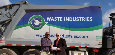 LEAP's Richard Garrett accepts a $5,000 check from Waste Industries General Manager Thane Harrison.