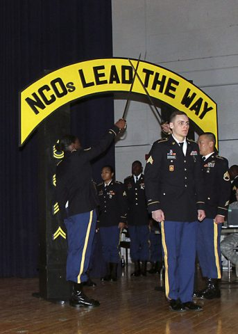 Sgt. Travis Bertovich, an intelligence analyst with 2nd Battalion, 44th Air Defense Artillery Regiment, 101st Airborne Division (Air Assault) Sustainment Brigade, 101st Abn. Div., walks through the golden arches, Feb. 2, 2017, during the brigade's noncommissioned officer induction ceremony at Wilson Theater, Fort Campbell, Kentucky. The ceremony is a time-honored tradition that welcomes the newly promoted NCOs to the Corps of the Noncommissioned Officer. (U.S. Army photo by Sgt. Neysa Canfield/101st Airborne Division Sustainment Brigade Public Affairs)