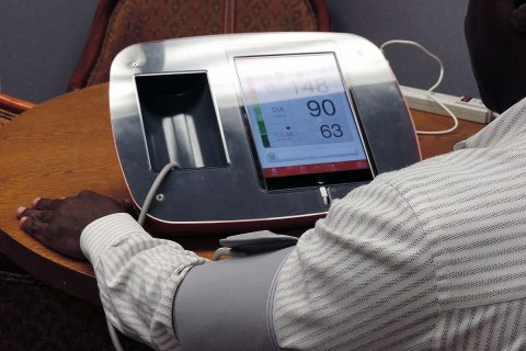 Man checking blood pressure at office kiosk. (American Heart Association)