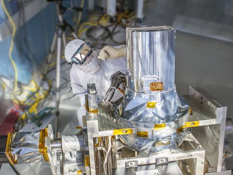 """NASA engineer Chip Holloway waits for the sun to align with the Stratospheric Aerosol and Gas Experiment III instrument during a clean room """"sun-look"""" test at NASA's Langley Research Center, Hampton, Virginia. SAGE III will measure aerosols and gases to better understand ozone in Earth's atmosphere. (NASA Langley/Sean Smith)"""