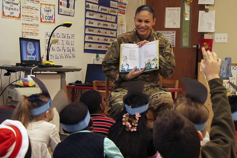 Pfc. Elise M. Fuentes, a military police with 218th Military Police Company, 716th MP Battalion, 101st Airborne Division (Air Assault) Sustainment Brigade, 101st Abn. Div., shows first grade students the illustrations in a book, March 2, 2017, during Read Across America Day at Marshall Elementary School on Fort Campbell, Kentucky. (Sgt. Neysa Canfield/101st Airborne Division Sustainment Brigade Public Affairs)