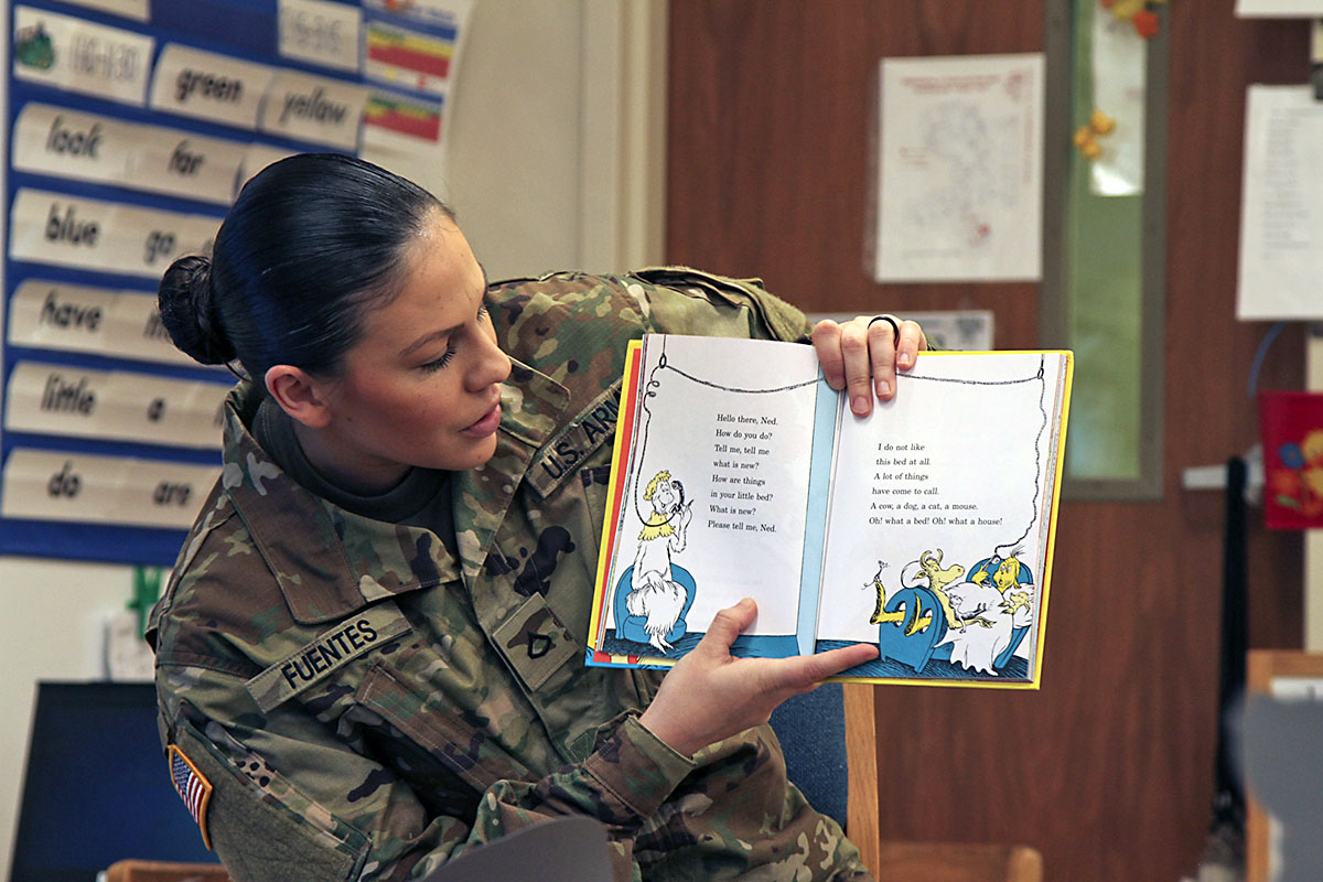 """Pfc. Elise M. Fuentes, a military police with 218th Military Police Company, 716th MP Battalion, 101st Airborne Division (Air Assault) Sustainment Brigade, 101st Abn. Div., reads """"One Fish, Two Fish, Red Fish, Blue Fish"""" by Dr. Seuss, March 2, 2017, to the first grade students of Marshall Elementary School on Fort Campbell, Kentucky. (Sgt. Neysa Canfield/101st Airborne Division Sustainment Brigade Public Affairs)"""