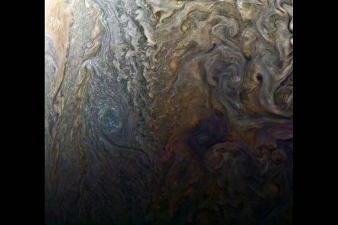 "This enhanced-color image of a mysterious dark spot on Jupiter seems to reveal a Jovian ""galaxy"" of swirling storms. (NASA/JPL-Caltech/SwRI/MSSS/Roman Tkachenko)"