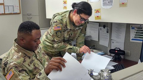Pfc. Detron R. Mitchell, left, and Spc. Iris I. Claros, right, consolidate documents Feb. 20, 2017, in the disbursing section of the Defense Military Pay Office for an inspection by the Network Audit Field Compliance Division of the Defense Finance and Accounting Service. (1st Lt. Todd A. Kuzma)