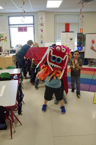 Students in Amanda Tejkowski's kindergarten class at Barasanti Elementary School huddled under their handmade Chinese dragon in preparation for the school's fashion show during International Day March 24, 2017. The kindergarten students worked tirelessly designing the dragon using pom poms, styrofoam, glitter and streamers. (Mari-Alice Jasper, Fort Campbell Public Affairs Office)