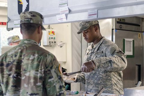 Spc. Ontroy Canty a food service specialist assigned to E Company, 6th Battalion, 101st General Support Aviation Battalion, 101st Combat Aviation Brigade, 101st Airborne Division, serves breakfast to Capt. Capt. Kris Sibbaluca in a containerized kitchen May 11, 2017 at Fort Campbell, Kentucky.  (Leejay Lockhart, Fort Campbell Public Affairs Office)