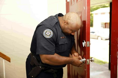 Clarksville Police Officers install child safe door knob covers to prevent the 2 year old from opening the door. (Jim Knoll, CPD)