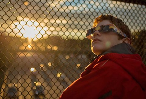 A boy wearing protective viewing glasses watches a partial solar eclipse from Arlington, Virginia, in 2014. (NASA/Bill Ingalls)
