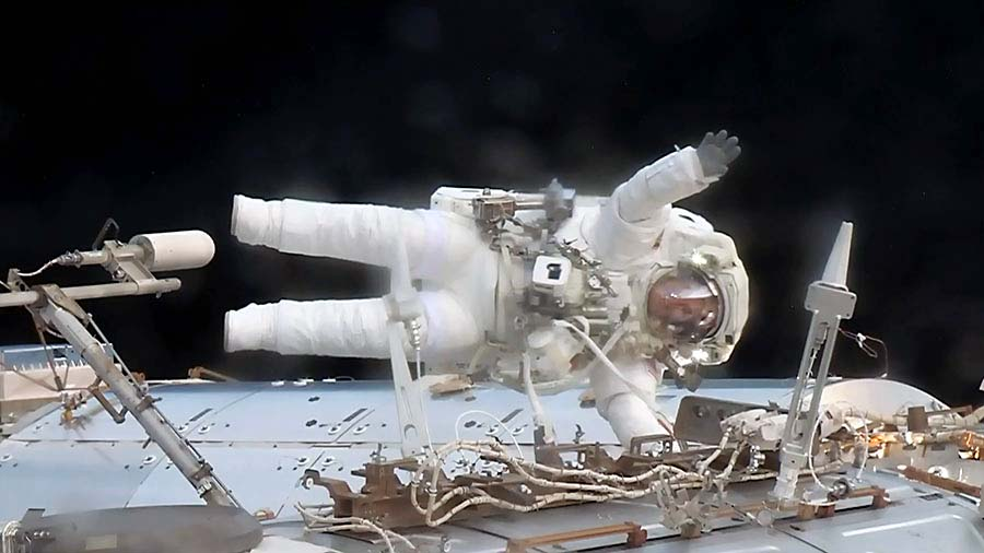 Astronaut Jack Fischer waves while attached to the Destiny laboratory during a spacewalk to replace a failed data relay box and install a pair wireless antennas. (NASA)