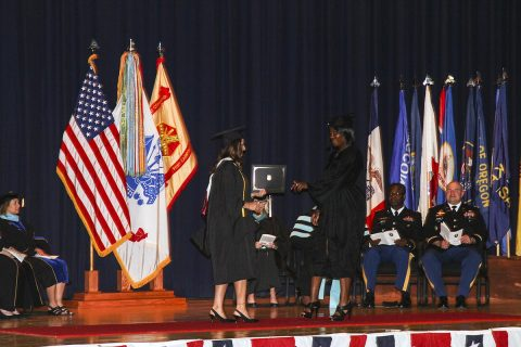Staff Sgt. Shenea Andrews, the chaplain assistant noncommissioned officer in charge for the 101st Airborne Division (Air Assault) Sustainment Brigade, 101st Abn. Div., walks across the stage of Wilson Theater, June 9, 2017, to receive her bachelor's degree during the joint graduation ceremony on Fort Campbell, Kentucky.  (Sgt. Neysa Canfield/101st SBDE Public Affairs)
