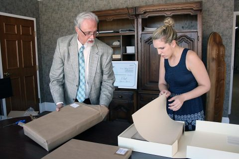 Customs House Museum Director Jim Zimmer and Curator of Collections Kali Mason examine the newly restored Civil War diary of Serepta Jordan. The diary was found in a smoke house near Clarksville and given to the Museum in 1984.