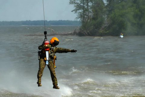 Sgt. Blake Armstrong, a flight medic with Company C, 6th Battalion, 101st Aviation Regiment, 101st Combat Aviation Brigade, uses a hoist June 29, 2017 near Scott Air force Base during over-water training. The training was used to simulate rescuing someone from a life raft while stranded in open water. (Sgt. Marcus Floyd, 101st Combat Aviation Brigade)